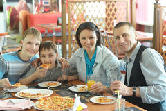 Family eating pizza. Portrait of a cute family eating pizza in cafe Stock Photos
