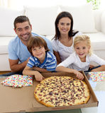 Family eating pizza on sofa Royalty Free Stock Photos