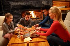Family eating pizza together for dinner royalty free stock photography