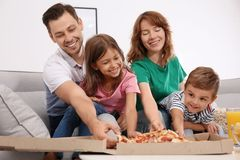 Family eating pizza while watching TV royalty free stock photos