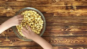 Family is eating popcorn from glass bowl, top view. Close-up video stock video