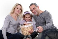 Family eating popcorn. On a sofa stock photos
