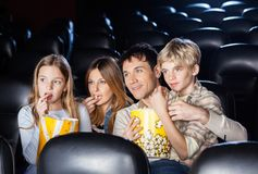 Family Eating Popcorn While Watching Film In. Family of four eating popcorn while watching film in movie theater Royalty Free Stock Photo