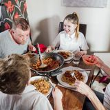 Family Eating Spagetti Bolognese Tgoether. British family enjoying a spagetti bolognese together at home. The children are laughing as their father has spagetti Royalty Free Stock Photo