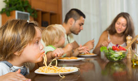 Family eating spaghetti. Happy family with playful little daughters eating with spaghetti at table. Focus on girl Royalty Free Stock Photography