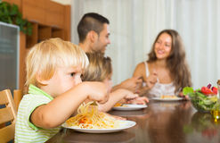 Family eating spaghetti. Happy young family eating with spaghetti at table. Focus on girl Stock Images
