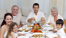 Family eating turkey in a celebration meal. Family eating turkey and vegetables in a celebration meal at home Stock Image