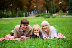 Family is eating a watermelon together in the park. stock photography
