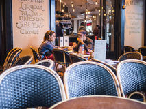 Family eats burgers at outside table at a cafe in Paris, France Royalty Free Stock Image