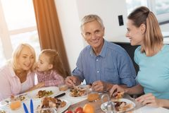 The family eats at the festive table for Thanksgiving. People are communicating. The family eats at the festive table for Thanksgiving. A men communicates with a Royalty Free Stock Photography
