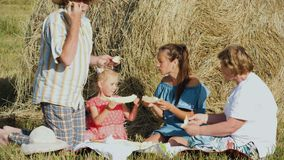 Family eats melon during picnic at the meadow. Multi aged family eats melon while having a picnic in the meadow. Mother with little daughter and her grandparents stock video