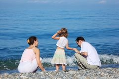 Family on edge of sea Stock Photos