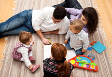 Family education group. Family group of five on the floor - two babies and three adults in the middle of a conversation Stock Photo