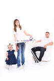Family efforts. Wife irons clothes.  husband has a rest, sitting in an armchair Royalty Free Stock Photos