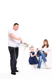 Family efforts. Husband irons clothes.  wife has a rest, sitting in an armchair Stock Image