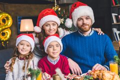 Family embracing on christmas. Young family embracing next to table with christmas dinner Stock Images