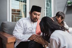 Muslim eid mubarak forgiving others. Family embracing each other during eid mubarak celebration. Forgiving by kneeling and pressing face to another`s knees royalty free stock photo