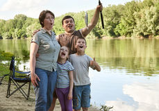 Family with emotion catch fish, people camping and fishing, leisure in nature, river and forest, summer season Stock Images