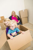 Family In Empty Room Playing With Moving Boxes Royalty Free Stock Photo