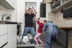 Family emptying the dishwasher Stock Photos