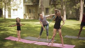 Family is engaged in fitness on a grass outdoors. Two little girls with her mother engaged in fitness on the grass near the house outdoors stock footage