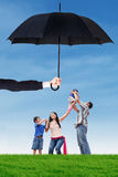 Family enjoy freedom at field under umbrella. Portrait of happy family playing and jumping together on the park under umbrella. Life and family insurance concept Royalty Free Stock Images