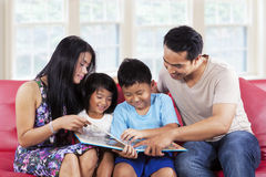 Family enjoy read a story book together. Portrait of hispanic family enjoy read a story book together at home Stock Photos
