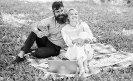 Family enjoy relax nature background. Couple bearded man and blonde woman relax nature while sit on green grass meadow royalty free stock images