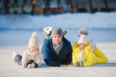 Family enjoy wintersport on ice-rink outdoors Stock Photos