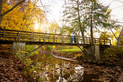 Family Enjoying Autumn Colors on a Park Bridge Stock Images