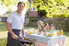 Family Enjoying A Barbeque. Smiling Royalty Free Stock Images