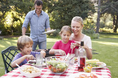 Family Enjoying Barbeque In Garden Together Royalty Free Stock Images