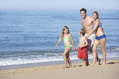 Family Enjoying Beach Holiday Running Along Beach Royalty Free Stock Images