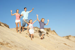 Family Enjoying Beach Holiday Running Down Dune. In The Sun Stock Photo