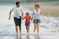 Family enjoying beach lifestyle. Family excercising at the beach, running along the waters edge late afternoon stock images