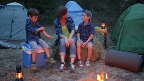 Family enjoying camping in forest, mother and two children sitting around on straw bale beside balefire, mom and kids stock video footage