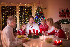 Family enjoying Christmas dinner at home. Big family with three children celebrating Christmas at home. Festive dinner at fireplace and Xmas tree. Parent and stock images