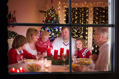 Family enjoying Christmas dinner at home. Big family with three children celebrating at home. Festive dinner at fireplace and Xmas tree. Parent and kids eating stock photography