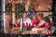 Family enjoying Christmas dinner at home. Big with three children celebrating at home. Festive dinner at fireplace and Xmas tree. Parent and kids eating at fire stock image