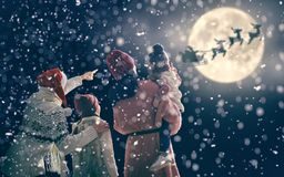 Family enjoying Christmas. Merry Christmas and happy holidays! Cute little children with mom and dad. Santa Claus flying in his sleigh against moon sky. Family stock photo