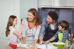 Family enjoying while cooking food in kitchen Royalty Free Stock Photos