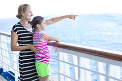 Family enjoying a cruise vacation together. A mother points out across the horizon to her cute daughter. The two are enjoying a family cruise ship vacation Royalty Free Stock Images