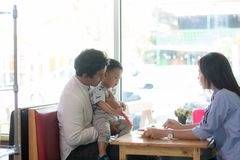 Potrait of asian family sitting inside  enjoying the day at cafe in the morning. Potrait of asian family sitting inside a cafe eating and playing a cake enjoying stock images
