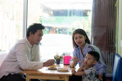 Potrait of asian family sitting inside enjoying. Potrait of asian family sitting inside a cafe eating and playing a cake enjoying the day in the morning royalty free stock images