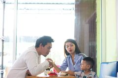 Potrait of asian family sitting inside a cafe eating and playing a cake enjoying. The day in the morning stock image
