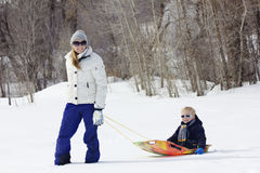 Family enjoying a day Snow sledding Stock Image