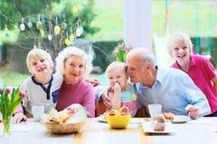 Family enjoying easter breakfast. Family of 5: grandparents and grandchildren, teenage boys and toddler girl eating eggs and pastry enjoying family breakfast on Stock Photo