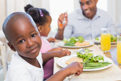 Family enjoying a healthy meal together with son smiling at camera Royalty Free Stock Image