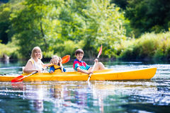 Family enjoying kayak ride on a river. Happy family with two kids enjoying kayak ride on beautiful river. Mother with little girl and teenager boy kayaking on Royalty Free Stock Photography