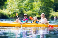 Family enjoying kayak ride on a river. Happy family with two kids enjoying kayak ride on beautiful river. Mother with little girl and teenager boy kayaking on Stock Photos